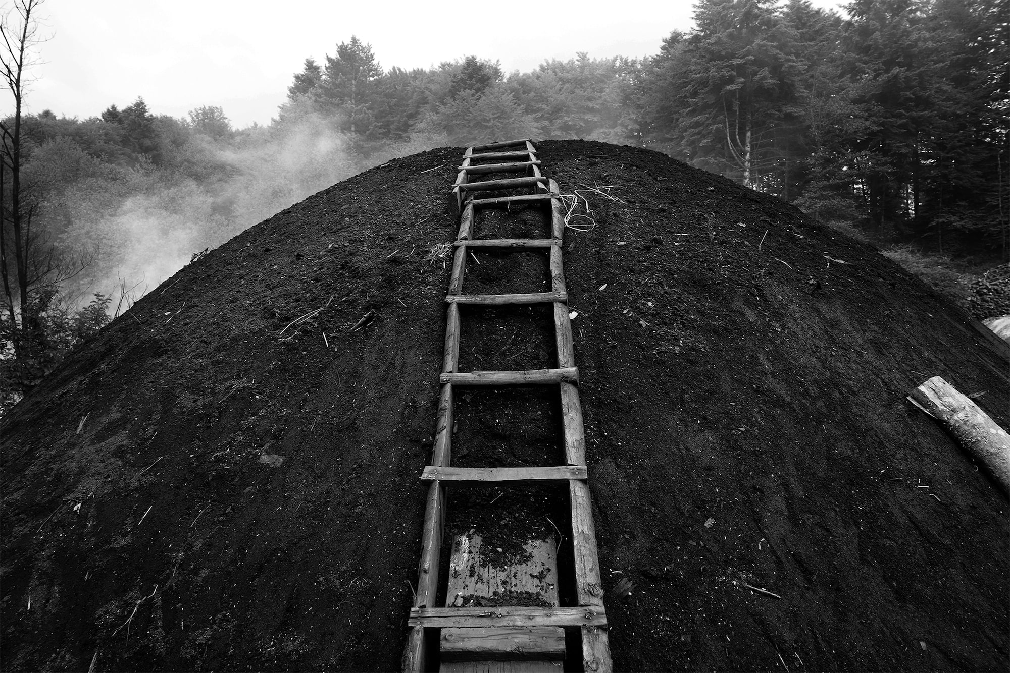 luigi baldelli sony alpha 7rIII a ladder leaning against a pile of burning charcoal