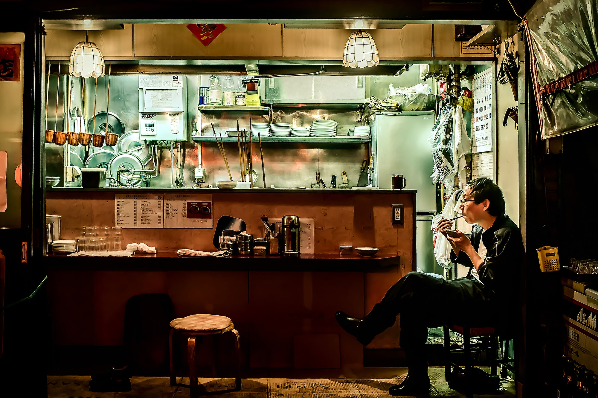 gabor erdelyi sony alpha 7RII man sits under moody lighting in kitchen eating with chopsticks