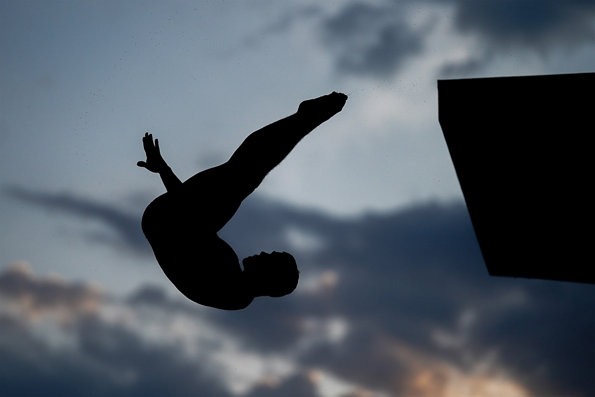 bob martin sony alpha 9II a diver leaps from a tall diving board silhouetted against a moody sky