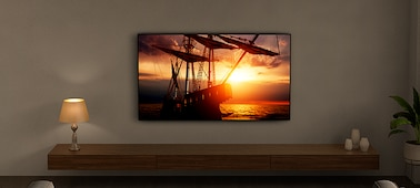 TV on a wall showing a ship at sunset