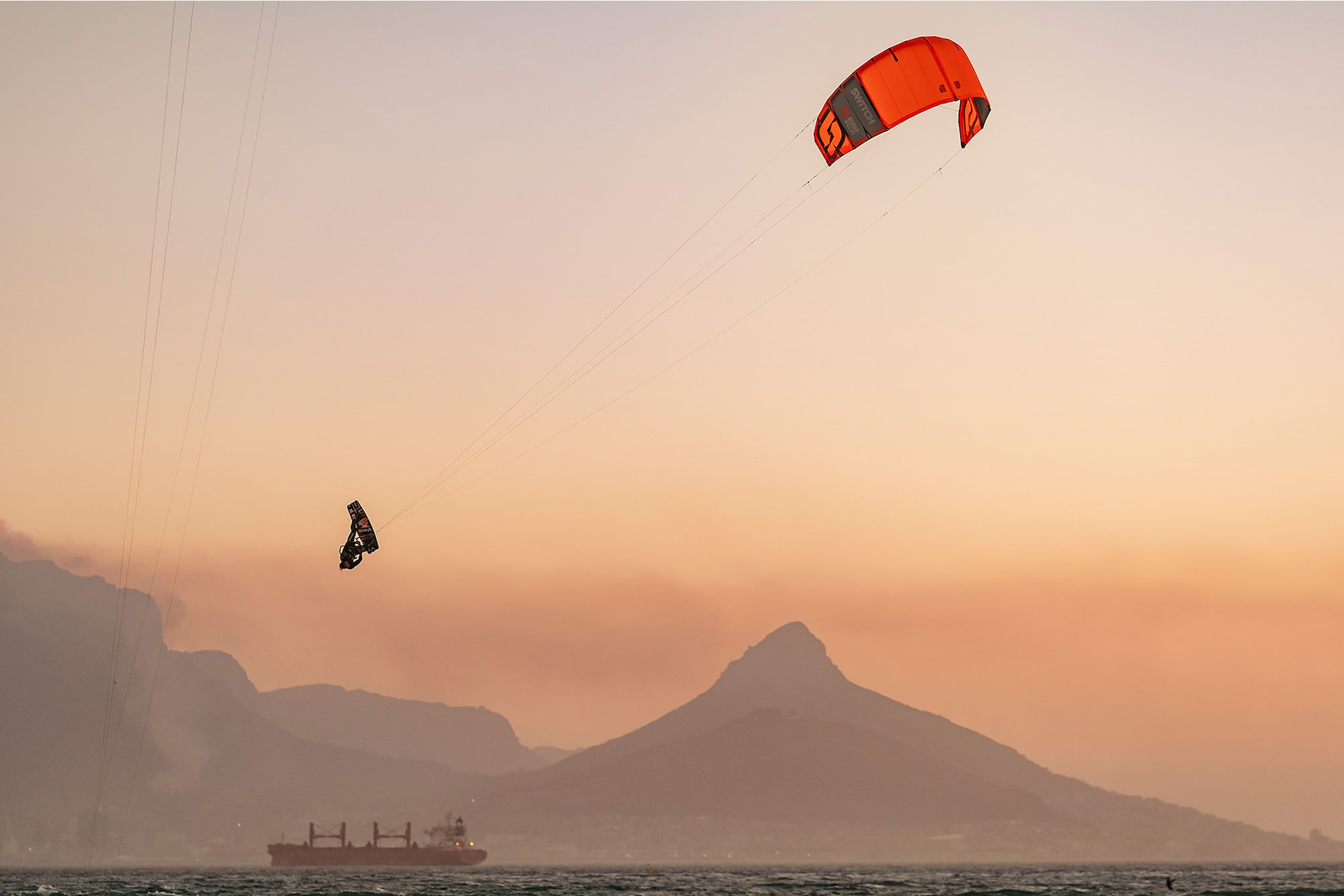 danas macijauskas sony alpha 7III kite surfer at dusk above the ocean with a ship in the background