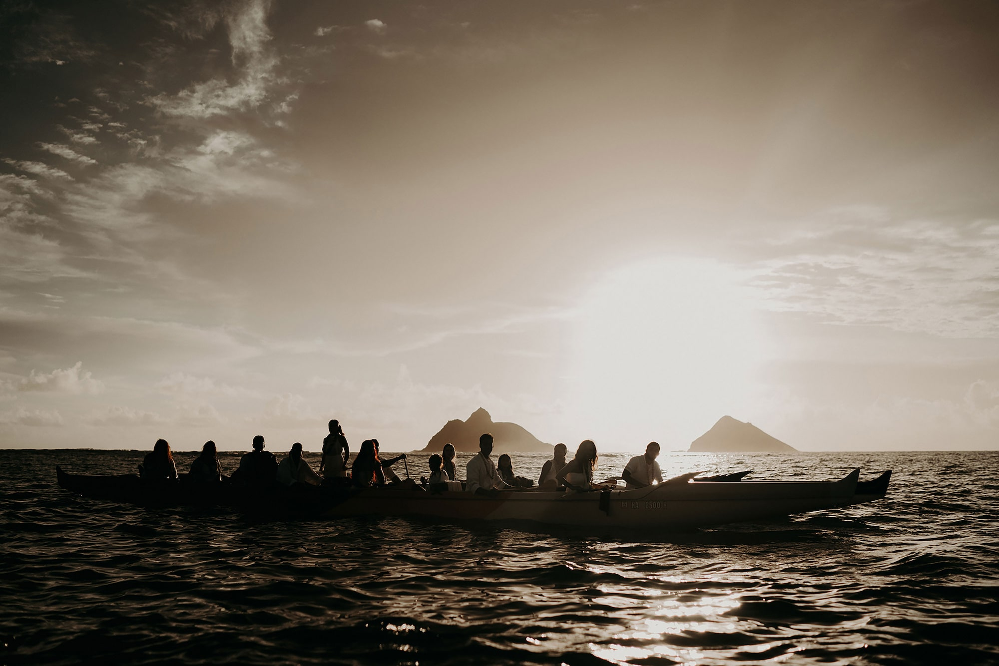 the quirky sony alpha 9 silhouette of people in a boat with mountains in the distance