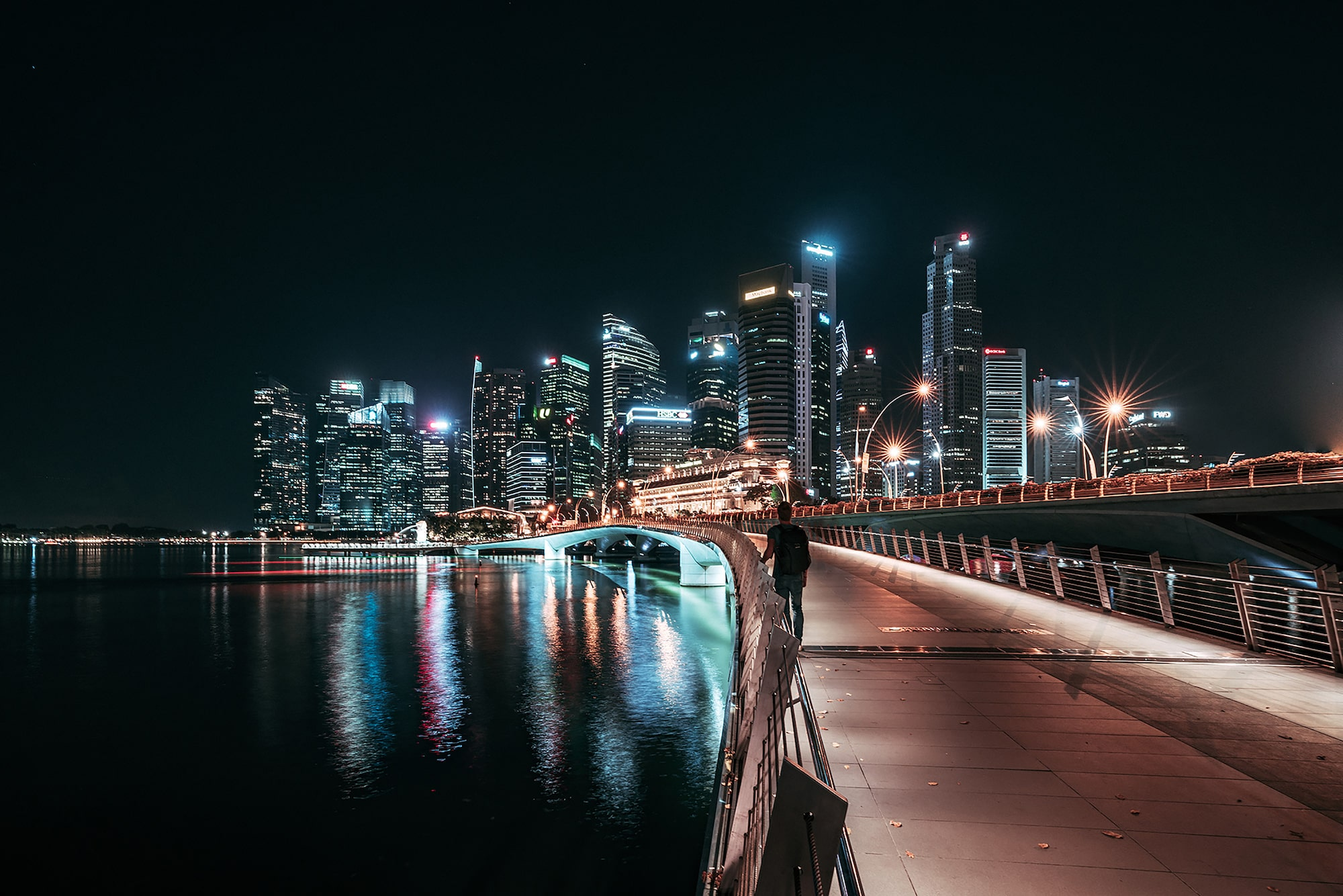 guillaume uchon sony alpha 7RIII a man walks across a bridge in singapore at night with skyscrapers on the horizon