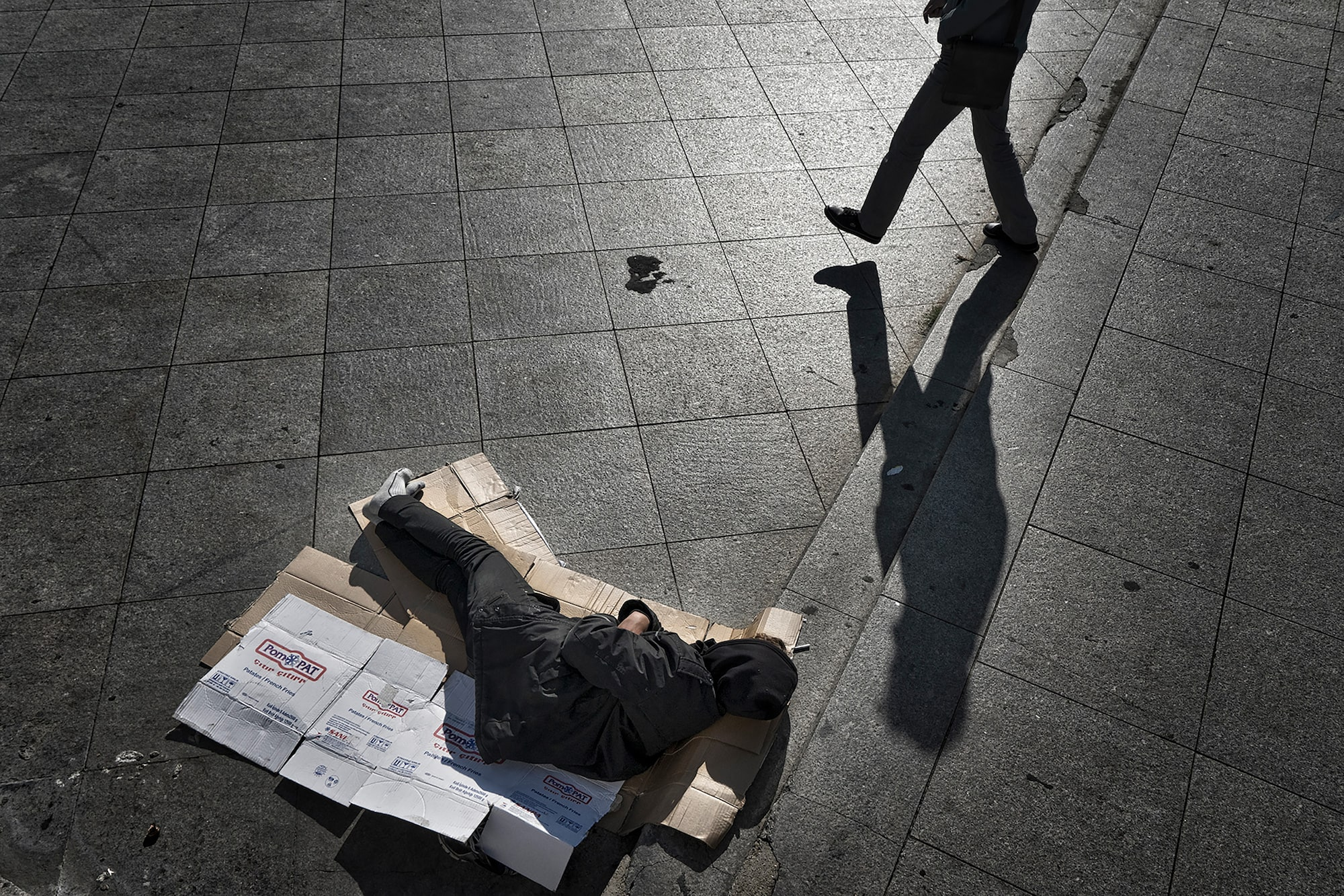 murat pulat sony alpha 7II homeless person lying on a bed of cardboard in the streets of istanbul