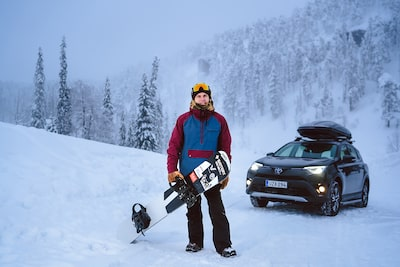 jaakko posti sony alpha 9 snowboarder poses with snowboard and car against snowy scene