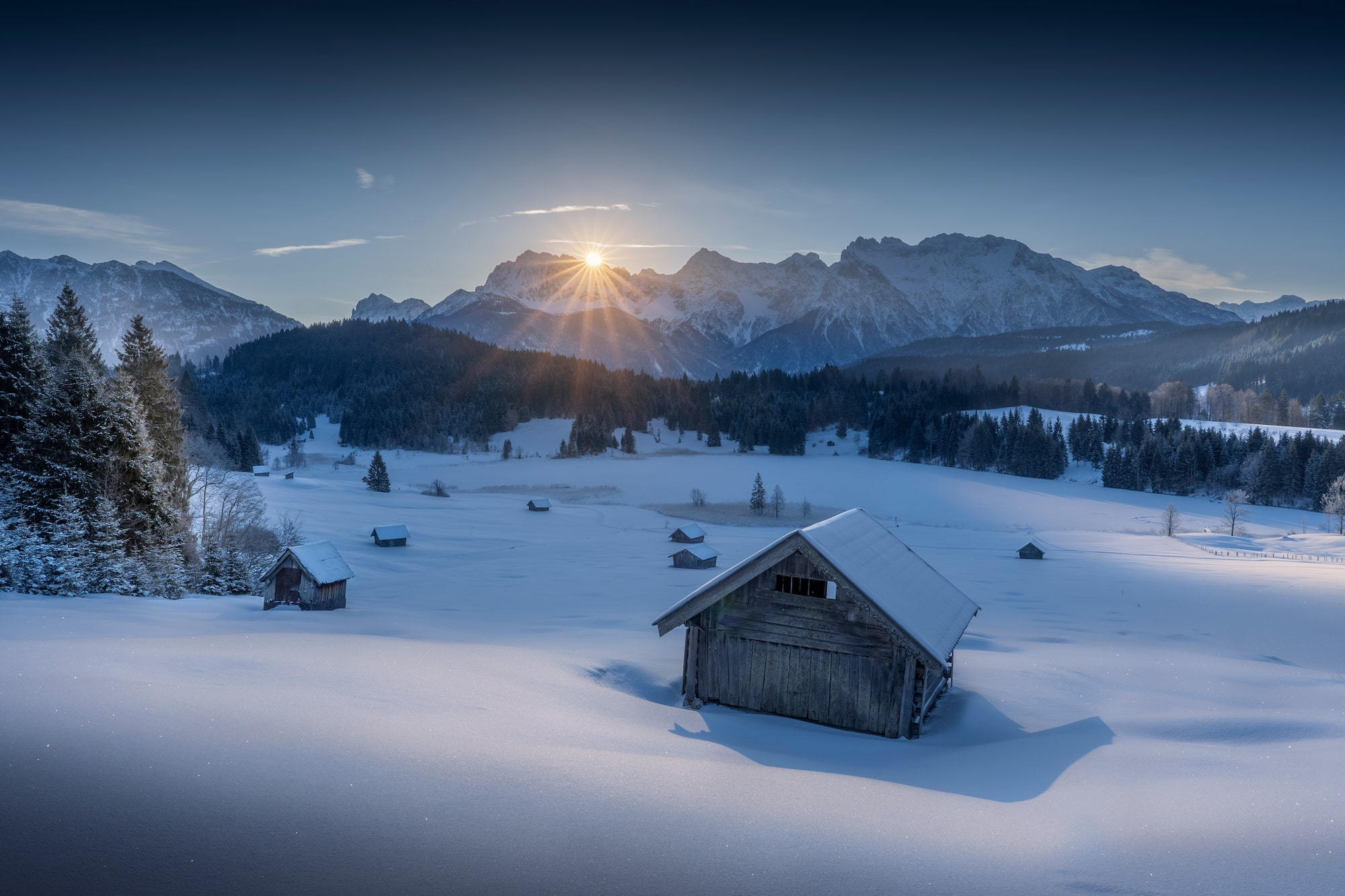 ilhan eroglu sony A6600 dawn breaks over a snowy scene with a wooden hut illuminated in the foreground