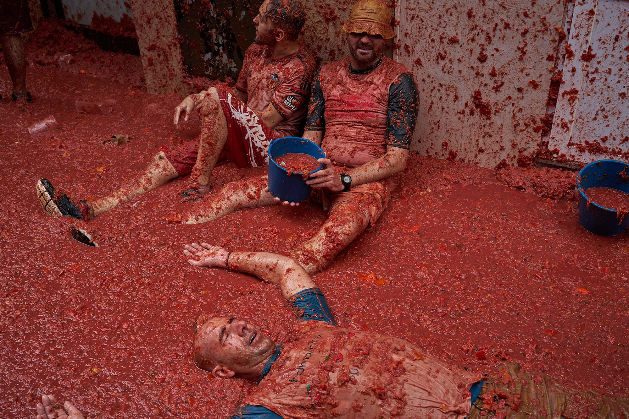 samuel aranda sony alpha 7RII revellers at the tomatina festival relax in pools of tomato remains