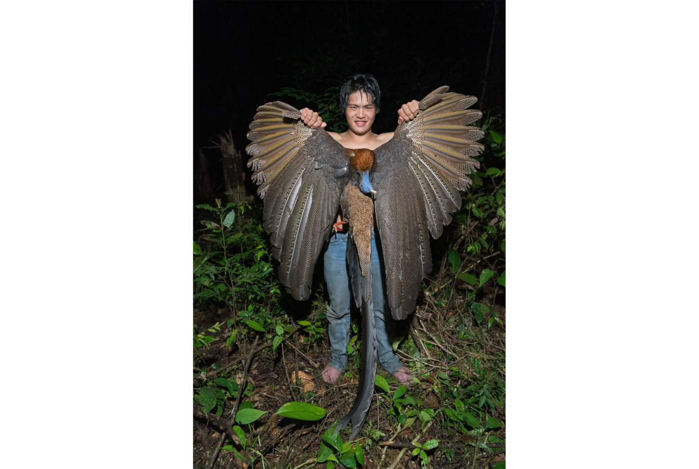 Tomas Wuethrich sony alpha 9 man holding a large bird at arms length with its wings spread