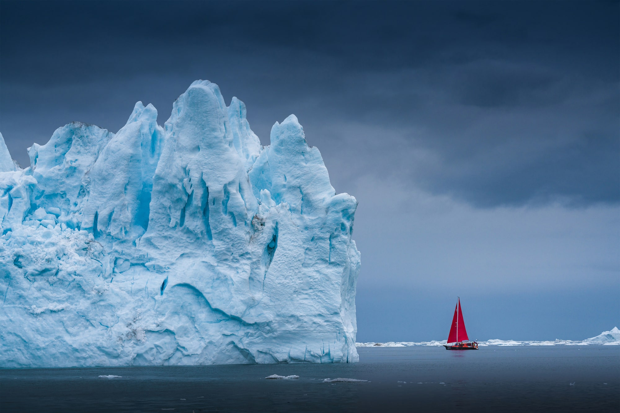 albert dros sony alpha A7RM4 boat with red sail sits next to a huge iceberg