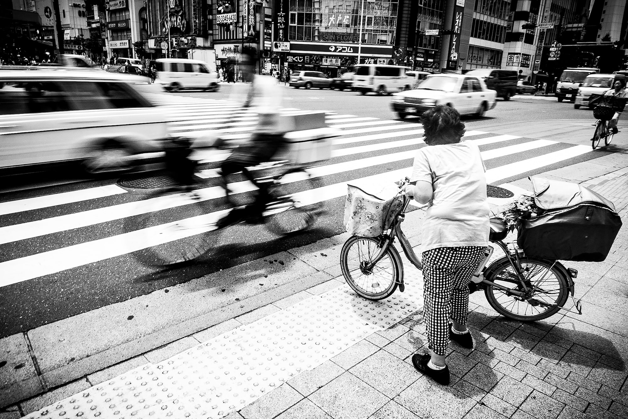 marek arcimowicz sony rx100V cyclist zooms past as a lady tries to cross a busy road