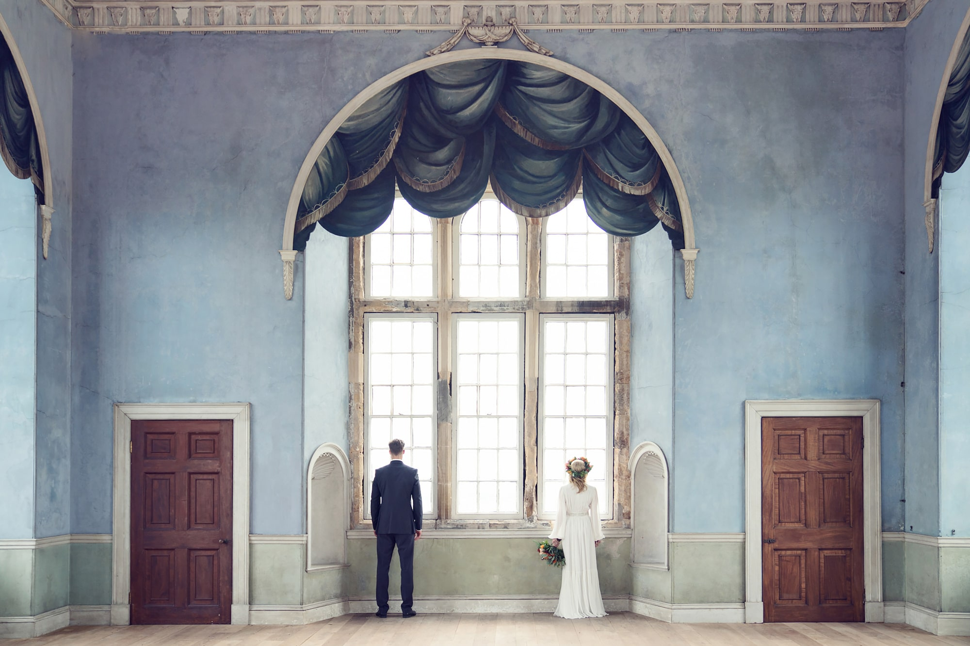 kate hopewell smith sony alpha 9 bride and groom stand facing the window in a perfectly symmetrical room