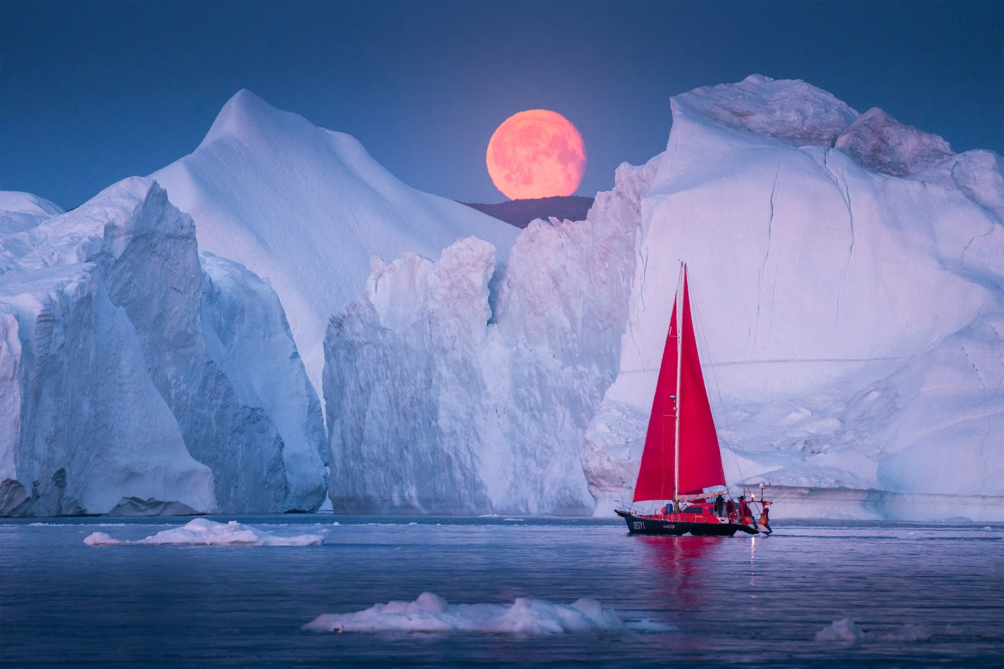 albert dros sony alpha A7RM4 the moon rises above an iceberg with a red sailed ship in the foreground